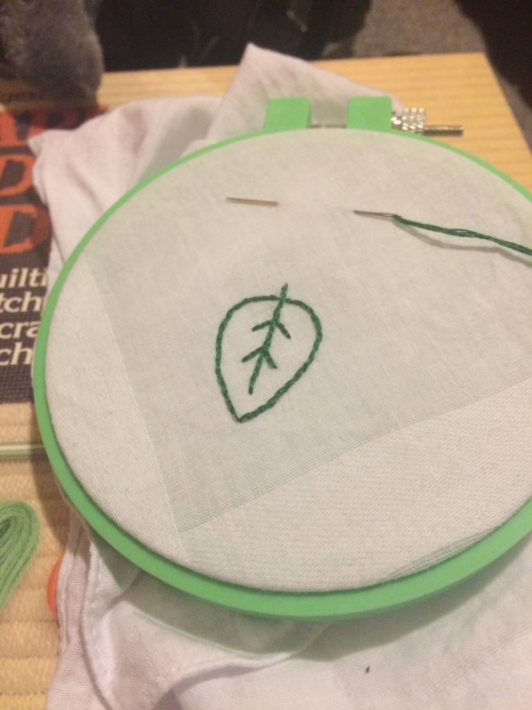 a little green leaf embroidered onto a white handkerchief corner