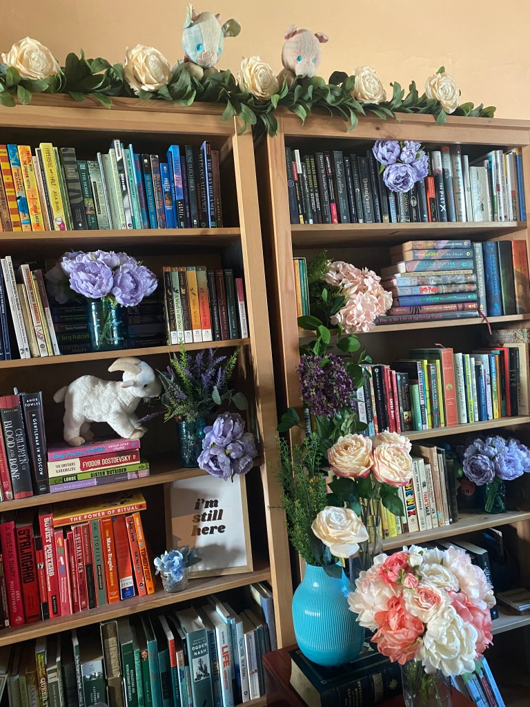 Wedding backdrop - bookshelves organized by color, with all sorts of silk flowers arranged artfully among the books.
